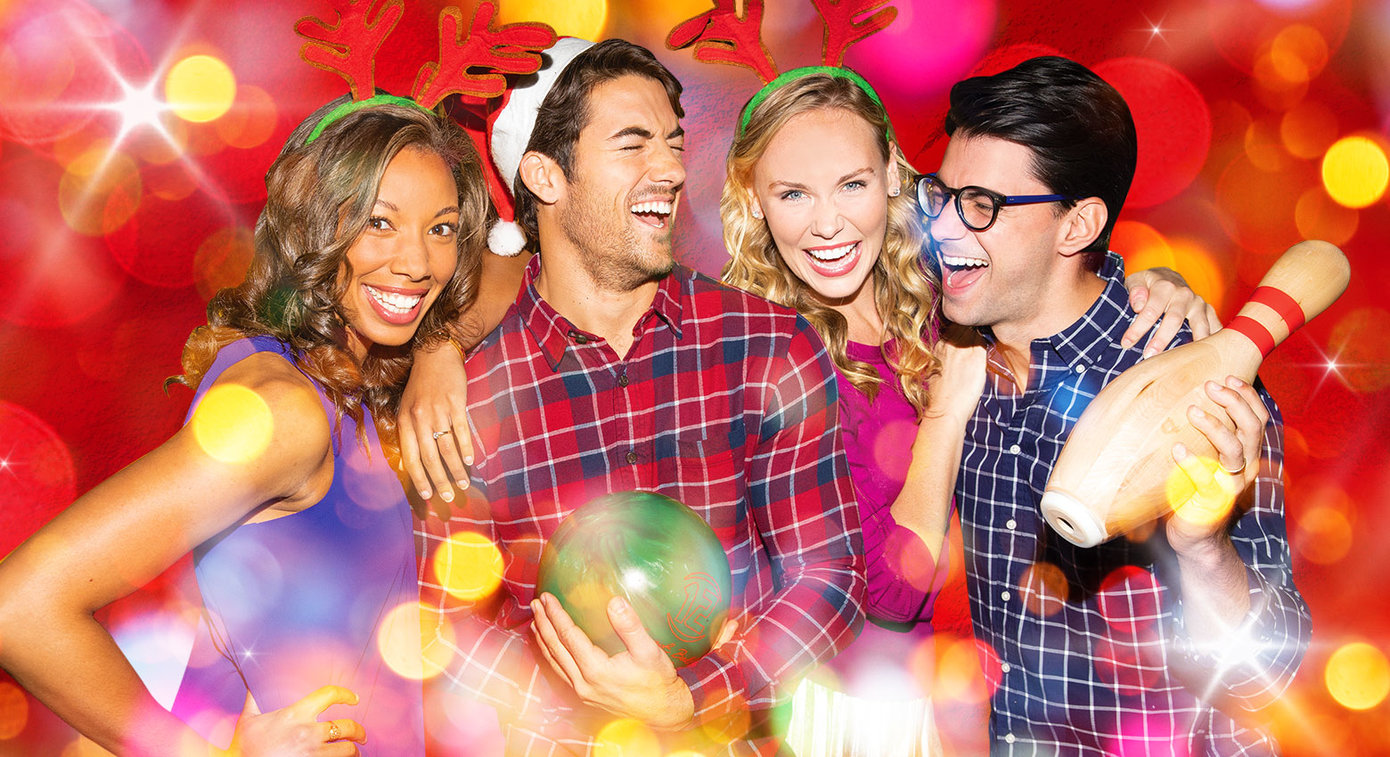 four friends laughing together in holiday clothes with a bowling ball and pin