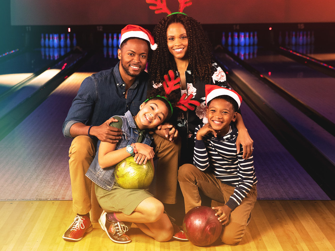 Family holding bowling balls and smiling on the lanes while wearing festive Christmas hats