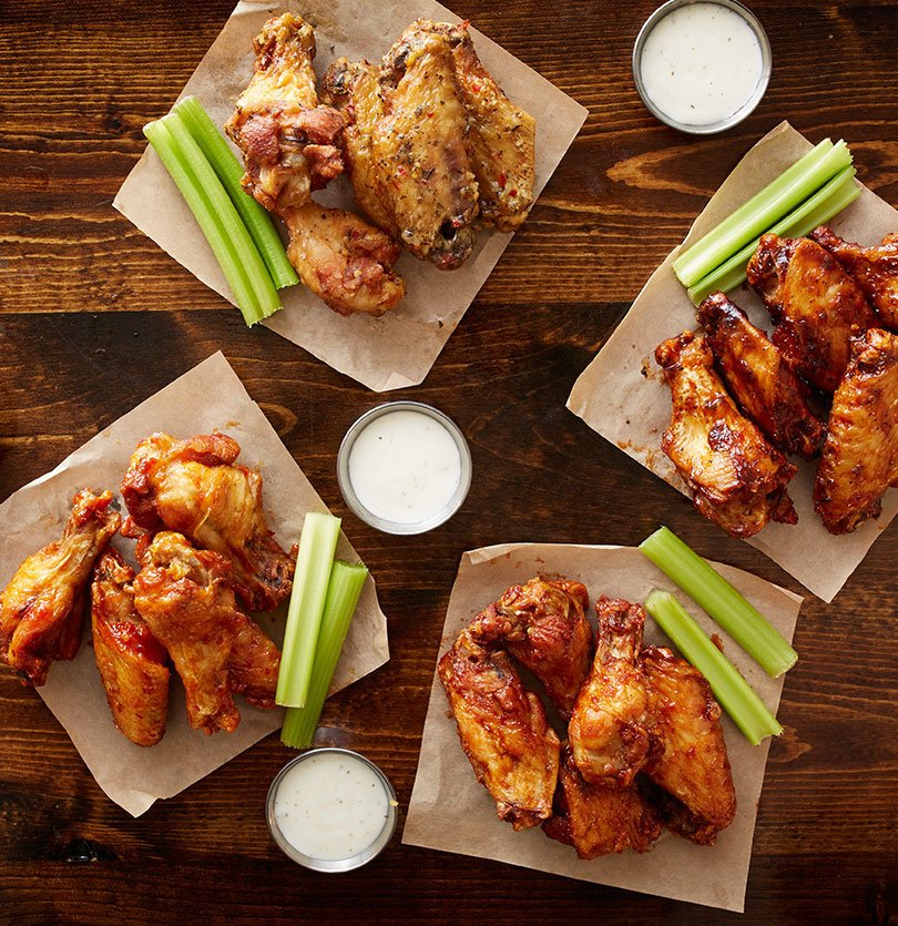 Four portions of chicken wings with different sauces and celery