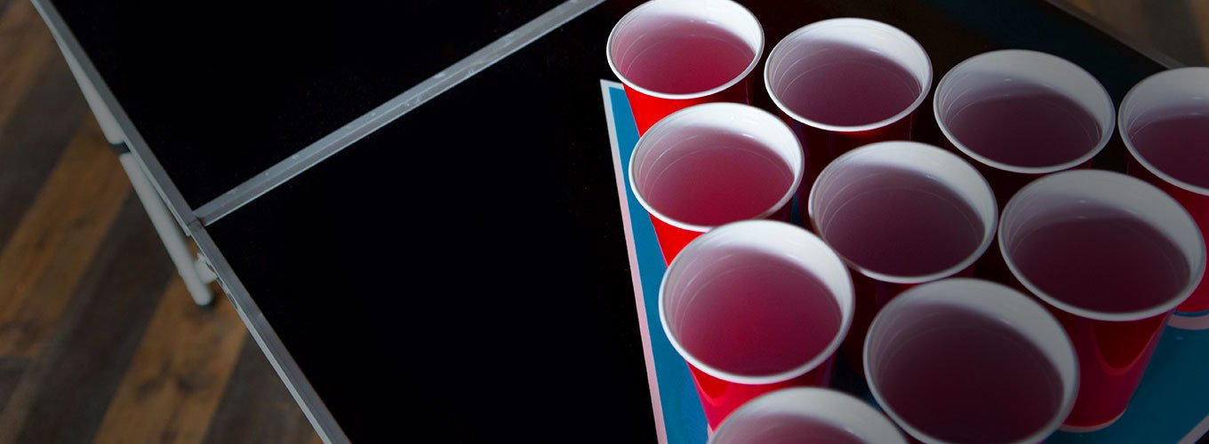 a triangle of red solo cups on a table