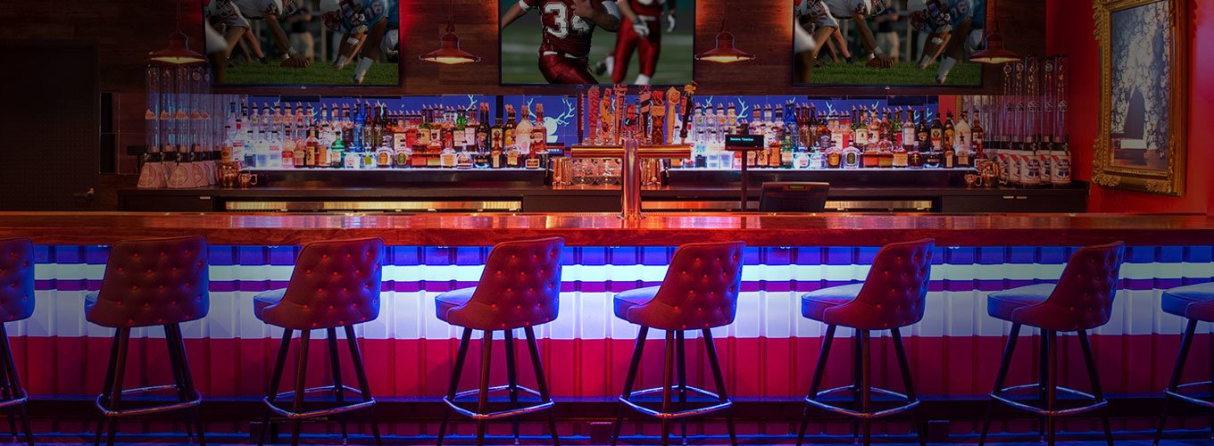 sports bar with red bar chairs, lit in neon